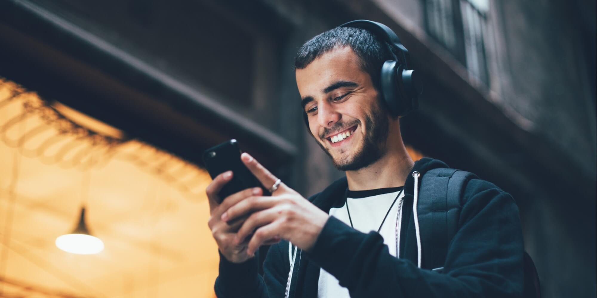 guy looking at phone while smiling